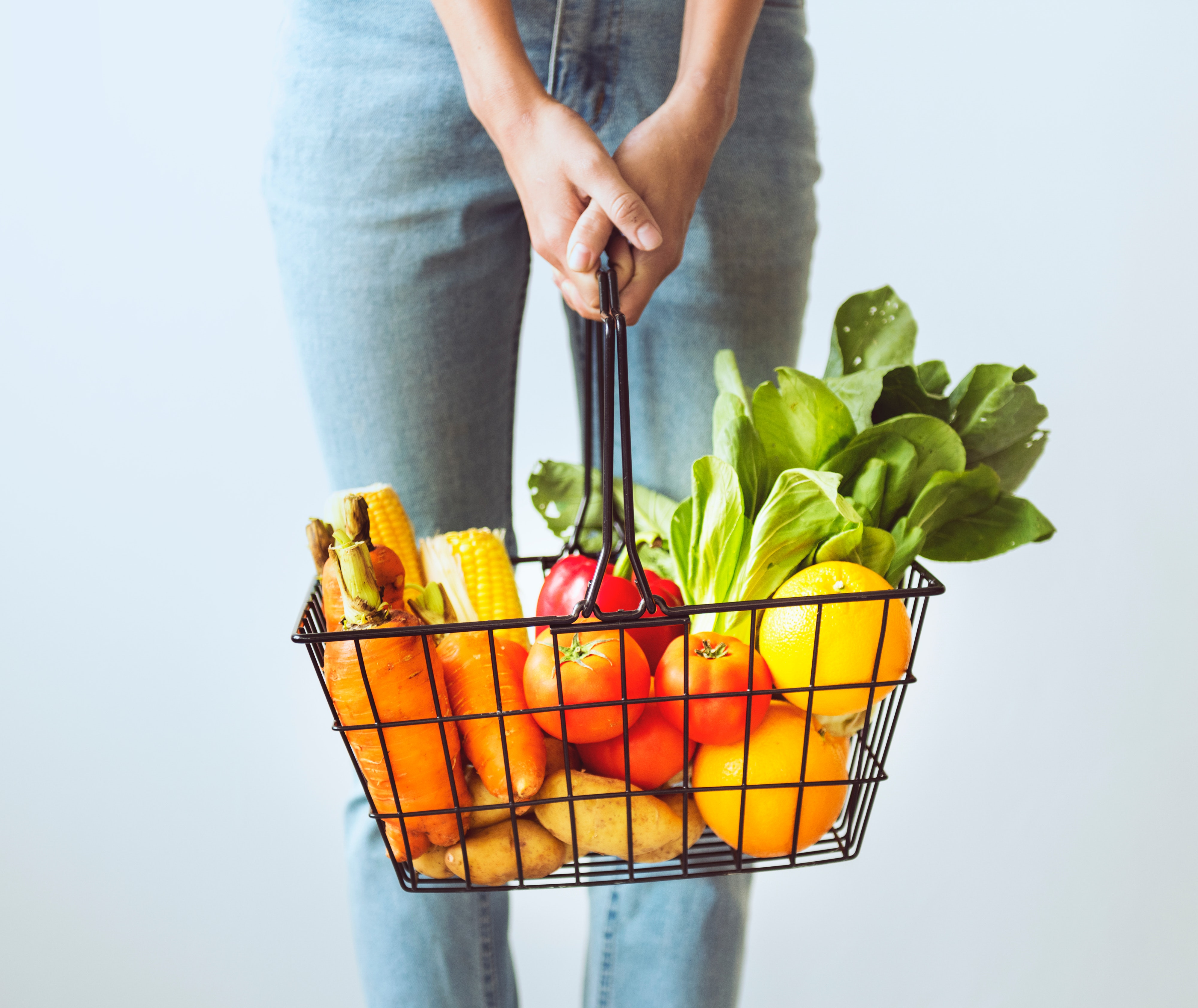 woman holding basket of fresh vegetables